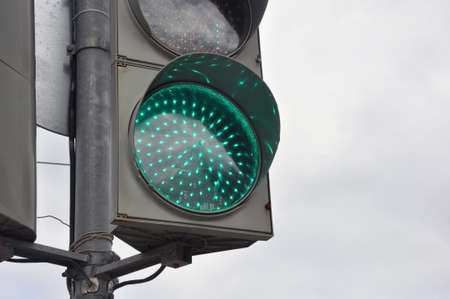 Green color at the traffic light with a gloomy sky in the background. Traffic adjustment. Stok Fotoğraf