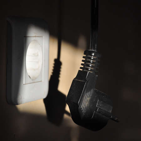 Wall outlet with a hanging plug in the sunlight.
