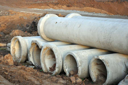 A wide-angle view of two rows of cement or concrete soil pipes lying on the ground, used to create sewage systems and aqueducts, against the backdrop of a construction site