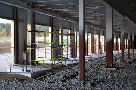 Construction of a warehouse complex, inside view. Columns are installed, crushed stone is laid on the floor.