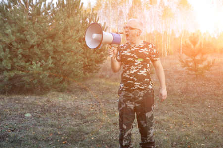 Portrait of a young man screaming with a megaphone in the forest. Lost People Search Concept. Outdoors