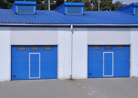 Blue rolling gates at the entrance to the warehouse building. Industry Imagens