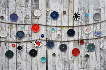 Interior Design. Old painted wooden wall with hanging plates and twine.