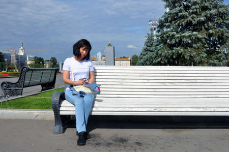 Outdoors lifestyle fashion portrait of a pretty young woman sitting smiling on a bench. Brick wall background. Wearing jeans, sneakers.