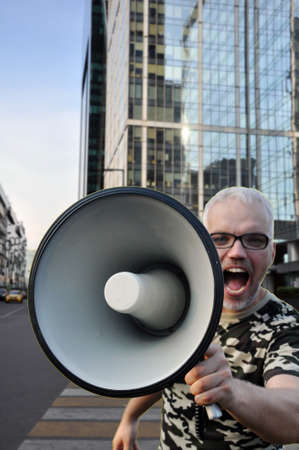 A man stands on a pedestrian walkway and shouted into a megaphone in the middle of a city street