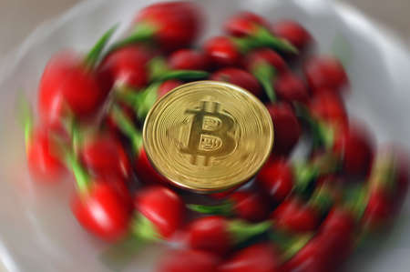 Golden bitcoin and red pepper on a white plate. Eating, Finance. radial blur