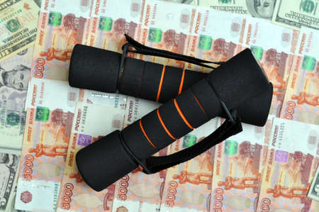 Dumbbells for fitness on the background of paper money, Russian rubles and dollars. Money swing concept