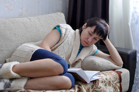 beautiful girl at home lying and reading a book. Relaxation