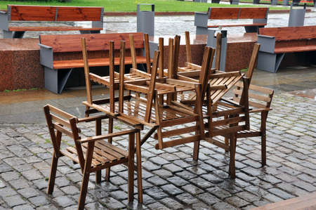 Wet tables and chairs on the city street outside the restaurant after the rain, closeup. 版權商用圖片