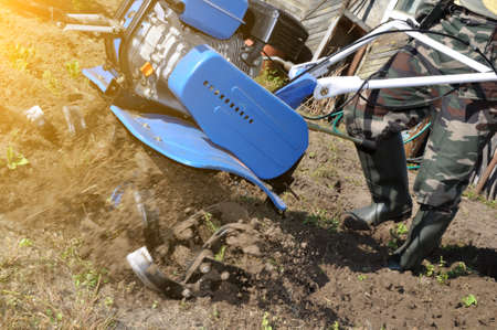 plowing the land in the garden with a cultivator. agricultural work on plowing the field for sowing seeds. a man plows the land with the help of motor cultivator. Stok Fotoğraf