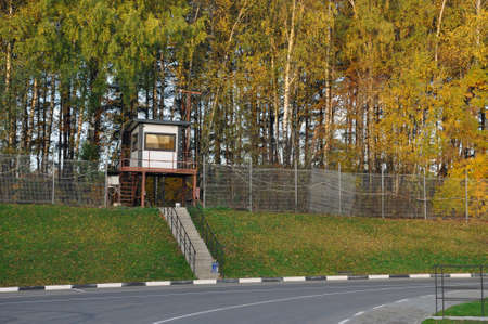 Security tower on the background of the autumn forest, controlled the territory of the modern logistics center in Moscow