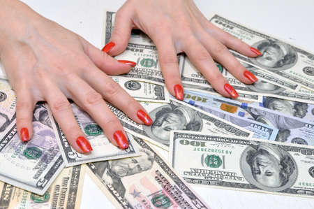 Female hands with long artificial manicured nails on a pile of money. U.S. dollars
