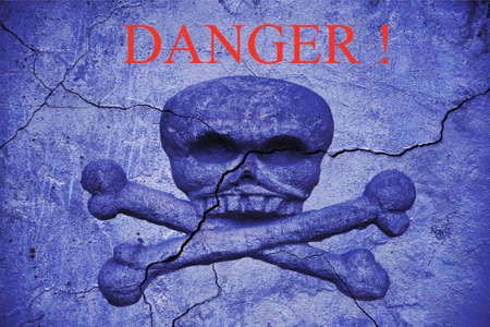 the word danger on an old cracked wall with a bas-relief of a skull and crossbones. Coronavirus infection concept Imagens