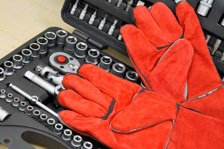 Red gloves on car repair tool kit, wrench set in natural light Stockfoto