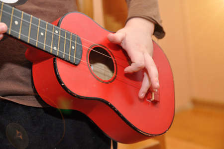 The child plays a children's guitar. Hand on musical instrument. A toy