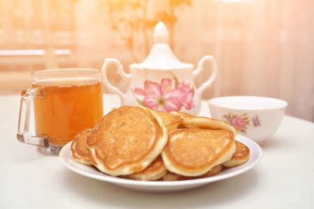 pancakes with sour cream, Shrovetide a large stack of fried pancakes with tea, selective focus, side view 版權商用圖片