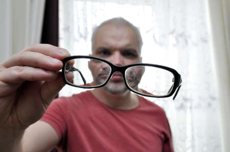 a man looks at the dirty lenses of his glasses. Out of focus.