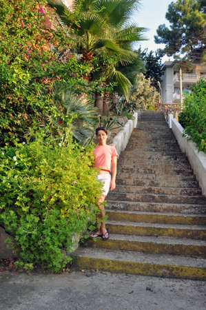 A young beautiful woman with short hair, in a pink T-shirt and white shorts, stands on a ladder surrounded by greenery and flowers. Spring or summer portrait. Banque d'images