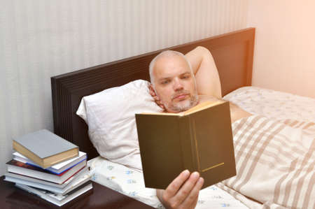 A young man on a Saturday morning reads a book in his bedroom. Self-isolation, COVID-19 Banque d'images