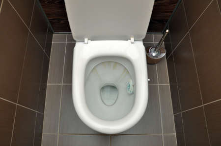 A white toilet with traces of rust from the flushing water. Hygiene Cleaning Banque d'images