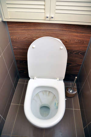 A white toilet with traces of rust from the flushing water. Hygiene