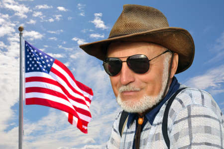 An American cowboy is standing against a blue sky with a developing American flag. Banque d'images