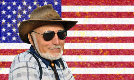 Portrait of not a young man in a cowboy hat and glasses with a gray beard against the background of the USA flag. Patriotism Banque d'images