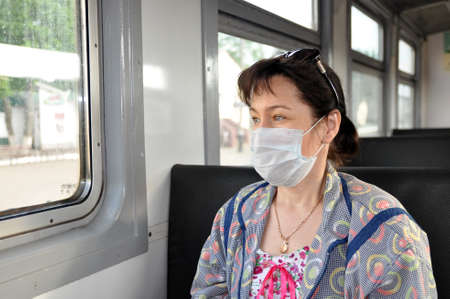 A woman in a medical protective mask rides in public transport. The concept of protection against respiratory infections, including coronavirus, COVID-19 Banque d'images