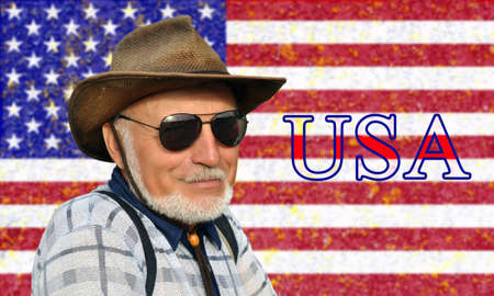 Portrait of not a young man in a cowboy hat and glasses with a gray beard against the background of the USA flag and the inscription USA. Patriotism