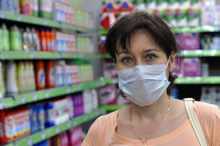 Young woman with a medical mask in a supermarket and looking at the camera. The concept of protection against coronavirus, COVID-19, and other respiratory infections.