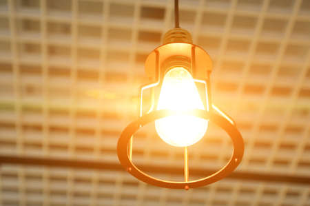 Incandescent lamp on the ceiling of the room, room lighting, creativity concept.