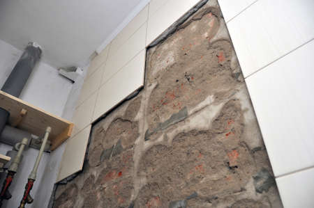 Wall of the toilet room with fallen off tiles, the defect of decoration, close-up view. 版權商用圖片
