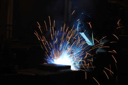The welder at the factory is engaged in the production of metal structures. Industrial welding