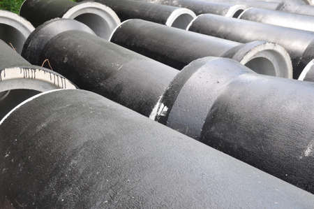 concrete pipes coated with protective mastic at a construction site. Stock
