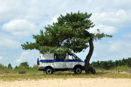 A police van under a lonely pine tree. Public order protection