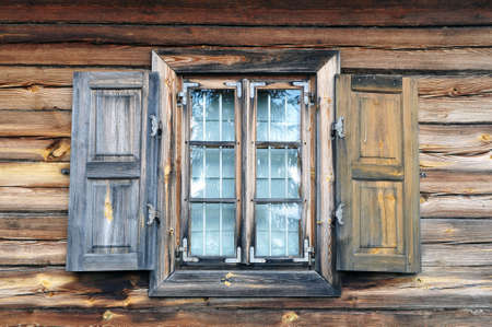 A shuttered window in an old country house. House walls made of natural timber with a window close-up. 版權商用圖片