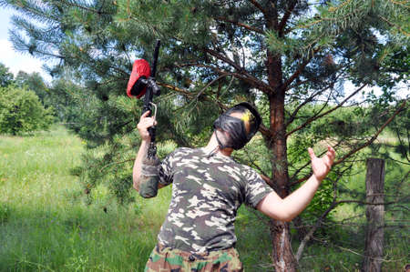 paintball player in camouflage uniform and protective mask was killed by the enemy in the head. Active games