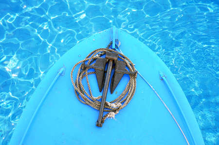 The bow of a boat floating on water with an anchor close-up on a sunny day