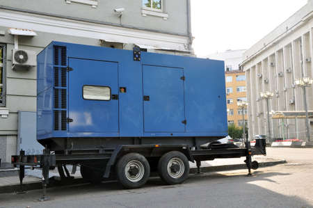 Blue standby mobile diesel generator for office building connected by cable wire to office building Stockfoto