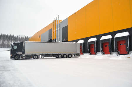 Delivery of goods by truck to a modern warehouse complex in winter.