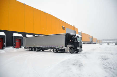 Moscow, Russian Federation - February 14, 2021: Delivery of goods by truck to a modern warehouse complex in winter.