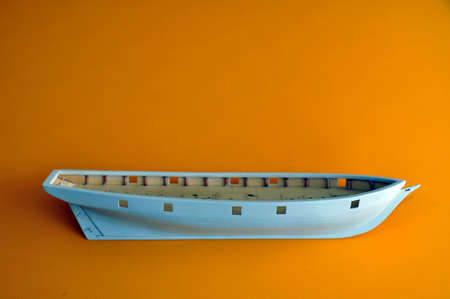 Making a model of a sailing ship, the hull of the ship on a yellow background. Hobby