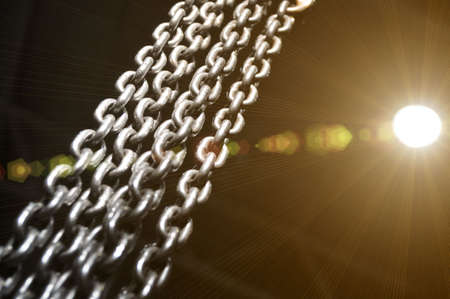 Metal chains dangling and illuminated with bright light. Industry.