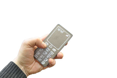A fake mobile phone made of a sheet of metal with drawn buttons and a monitor in a human hand, isolated. Banque d'images