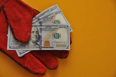US dollars in a red glove on a yellow background.