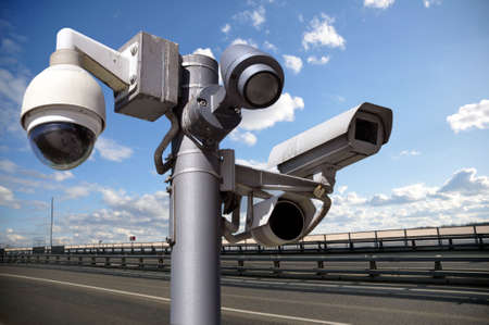 CCTV Security Camera or surveillance operating on traffic road and urban scene.