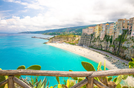Tropea town and Tyrrhenian Sea beach, colorful buildings on top of high big rocks, view from Sanctuary church of Santa Maria dell Isola with fence foreground, Vibo Valentia, Calabria, Southern Italy 写真素材
