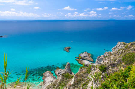 Aerial panoramic view of horizon and amazing tropical blue azure turquoise water of sea, rock cliff grass hill, Parco Belvedere platform Capo Vaticano, blue sky background, Calabria, Southern Italy