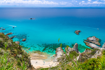 Aerial panoramic view of horizon and amazing tropical blue azure turquoise water of sea, rock cliff grass hill, rushing yachts boats, blue sky background, Capo Vaticano, Calabria, Southern Italy