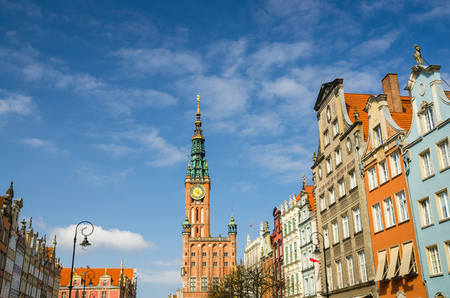 City Hall with spire, clock tower, facade of beautiful typical colorful multicolored houses buildings at Dluga Long Market street Dlugi targ square in old historical town centre, Gdansk, Poland
